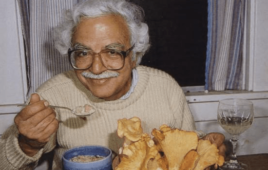 A smiling man eating mushroom soup.
