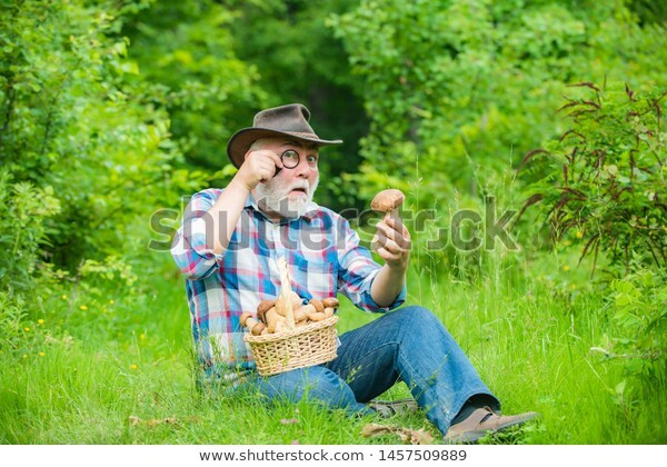 Old bearded man with a monocle, looking in astonishment at a mushroom.