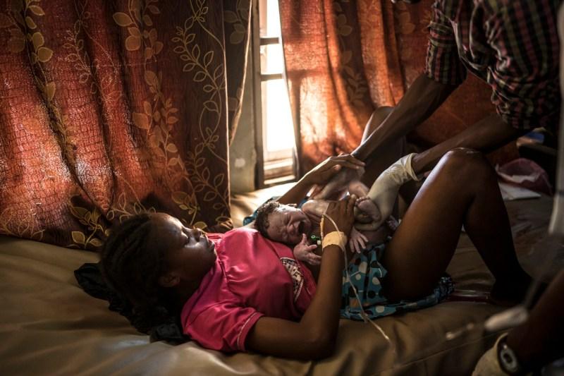 Алима Моду Бабайо впервые держит ребенка, спустя несколько секунд после родов, в Государственной специализированной больнице в Майдугури, Нигерия, 13 октября 2018 года.