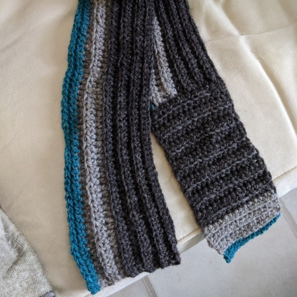 a crocheted scarf in grey and blue