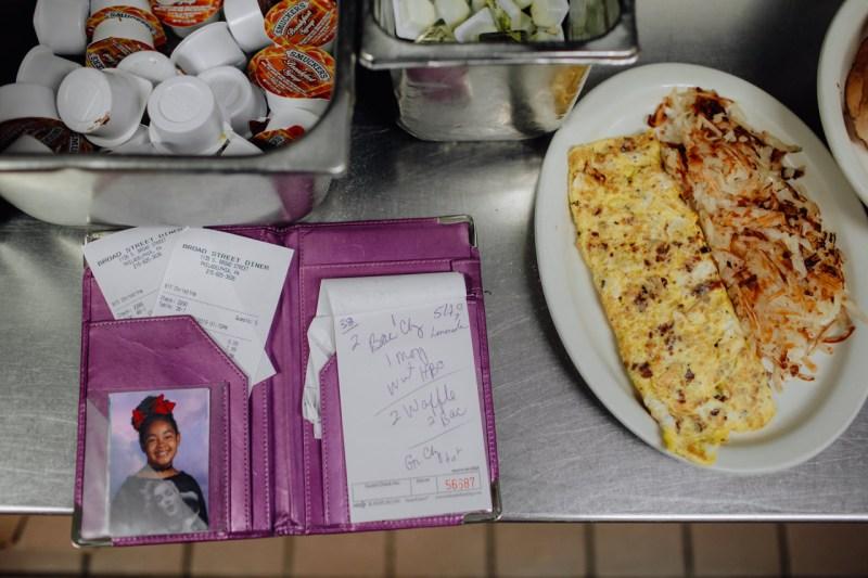 Официантка Кристина Манс на кухне в закусочной на Брод-стрит в Филадельфии держит фотографию своей дочери рядом с блокнотом для принятия заказов.