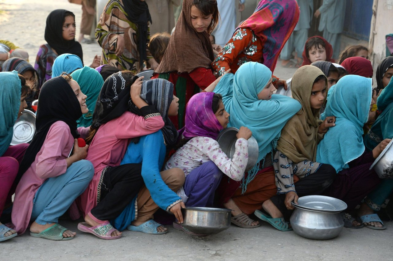 Jalalabad, Afghanistan Children wait in line with their empty bowls to receive food donations in the city Photograph: Noorullah Shirzada