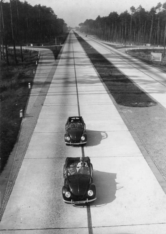 第二次大戦期のアウトバーンを走行する2台のKdFワーゲン(後のフォルクスワーゲン)。KdFは小型車ながらアウトバーンを100km/h連続巡航可能に設計され、1938年から戦時中にかけて少数が先行して限定製造された。短いスパンで打設されたコンクリート舗装が観察できる。1943年撮影