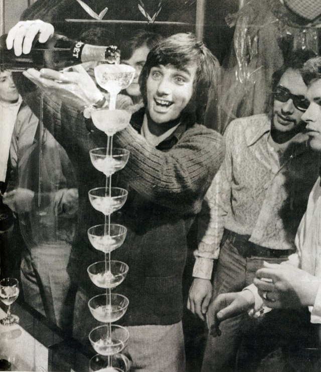 George Best filling some glasses with wine