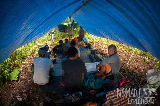 nowhere papua indonesia forest jungle wild wilderness tribal traditional culture travel adventure explore trek discover journey guide wonder dangerous survival village island tropical remote undiscovered tent tarp talking planning rain storm shelter