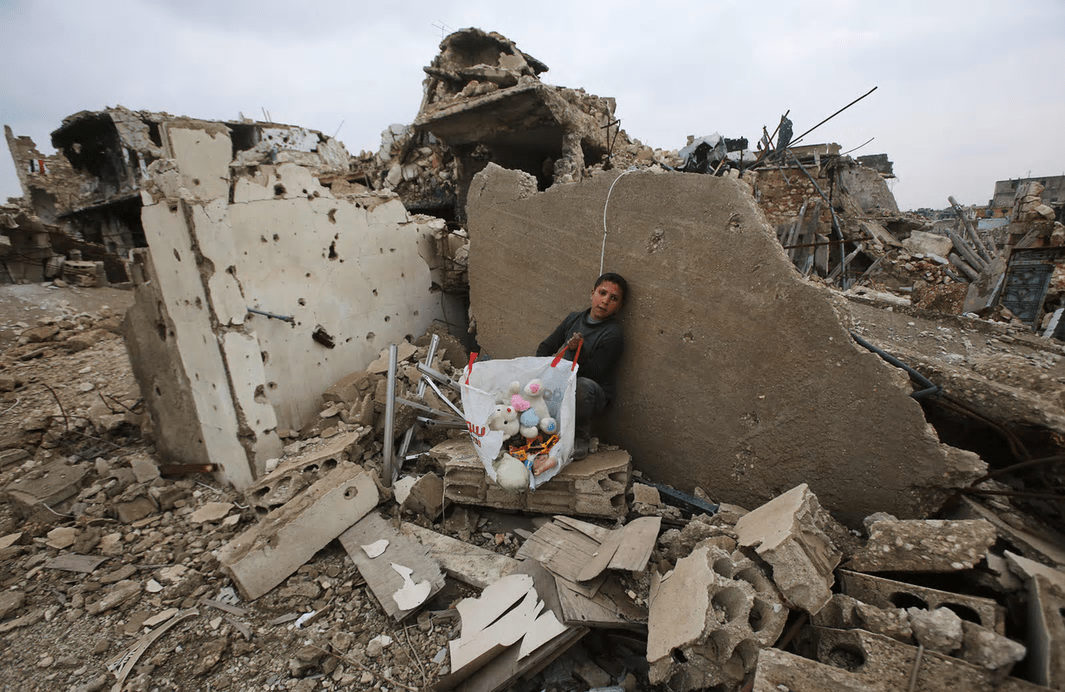 Aleppo, Syria A boy sits with belongings he collected from the rubble of his house in the Arkoub neighbourhood, after pro-government forces retook the area from rebel fighters Photograph: Youssef Karwashan