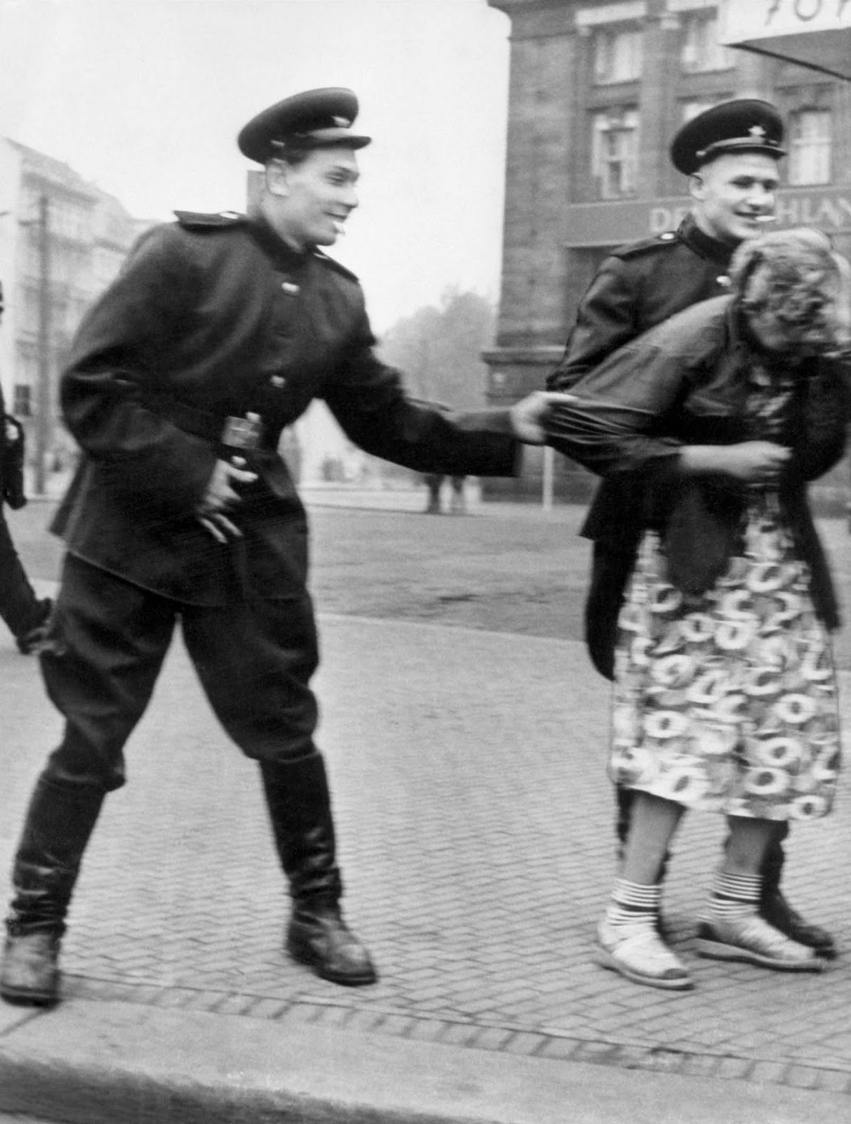 Soviet soldiers openly sexually harass a German woman in…