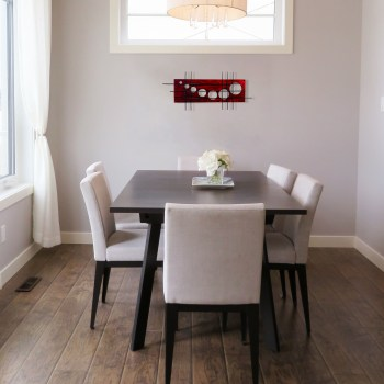 the neutral space of this dining room beautifully displays the aged red holy stix metal wall sculpture under the window