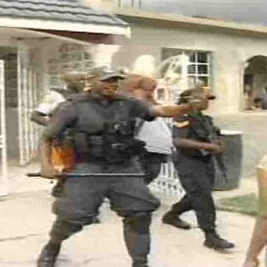 Jamaican police escort alleged homosexuals to safety, removing them from a house besieged by an anti-gay mobe. (Photo courtesy of Minority-Insight.org)