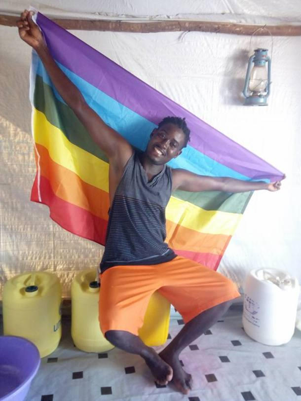 Moses Mbazira poses with a rainbow LGBT flag in his tent at Kakuma Camp. (Photo courtesy of Mbazira Moses)