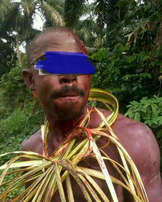 A victim mockingly dressed in palm leaves.