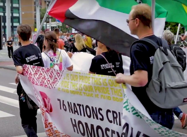 Banner at the front of  marchers carrying the flags of nations with anti-gay laws. (Photo courtesy of YouTube)