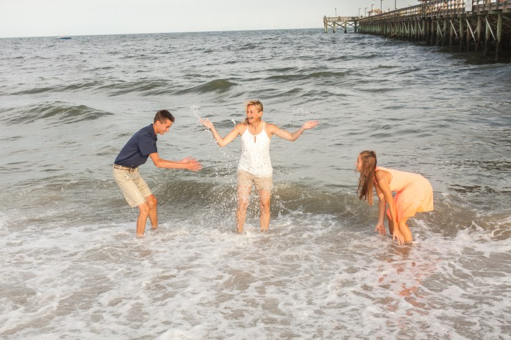 Family in the ocean getting beach pictures