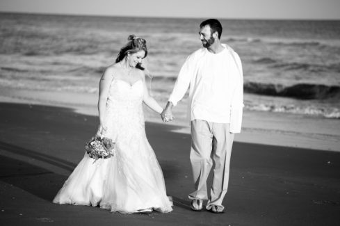 Bride & Groom hold hands walking on the beach