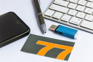 77 Design Co business card, keyboard, and flash drive.