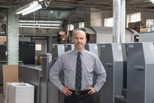 Interview-Paul Nickoloff Fotorecord. Image of Paul standing on the print production floor in a gray shirt and dark tie with his hands on his hips.
