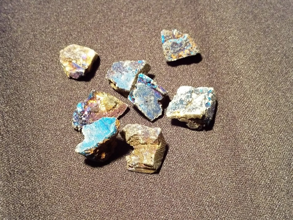 On a black background there are eight iridescent rocks shining in colors from grey to blue, purple, and gold.