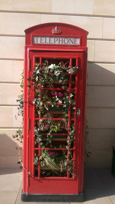 A red British telephone box is filled with flowers against a yellow stone background
