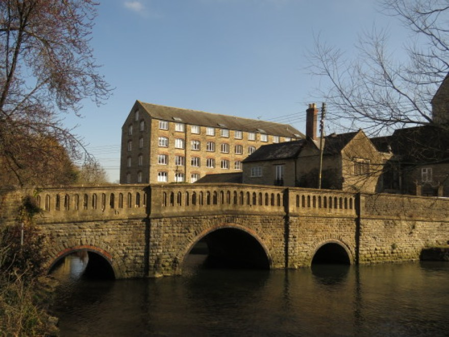 Malmesbury, England: A stone bridge crosses a river in the forgeound and a mill building with many windows sits in the background