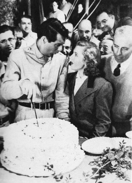 """Cary Grant slices a birthday cake presented to him on the set of Only Angels Have Wings with Jean Arthur, director Howard Hawks, and members of the camera crew watching."""