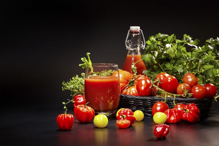 Glass of tomato juice with vegetables on black background