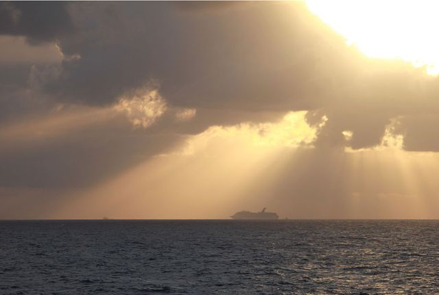 a boat in the distance on the gulf of mexico against a sunset