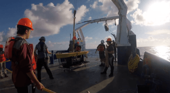 video still of a group of students in hard hats on a boat preparing to launch a yellow glider into the water