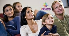 When Do You Show Your Homeschoolers Movies from Books They've Read? 7SistersHomeschool.com #MovieFirstOrBookFirst This photo shows a family watching a movie together at home.