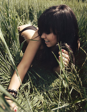 Beautiful girl with lovely fringe laying in a field