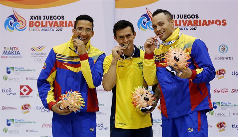 El colombiano Jossimar Calvo (c) posa con la medalla de oro de arzones, acompañado por los venezolanos Adickxon Trejo (i), plata, y José Fuentes (d), bronce, en gimnasia artística en los XVIII Juegos Bolivarianos. Foto: EFE