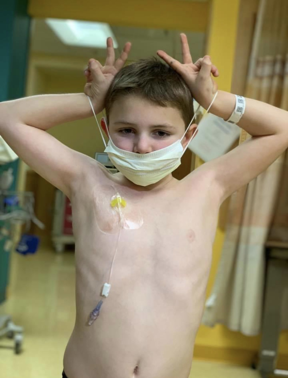 Sam wearing mask at hospital during cancer treatment doing peace signs with his hands