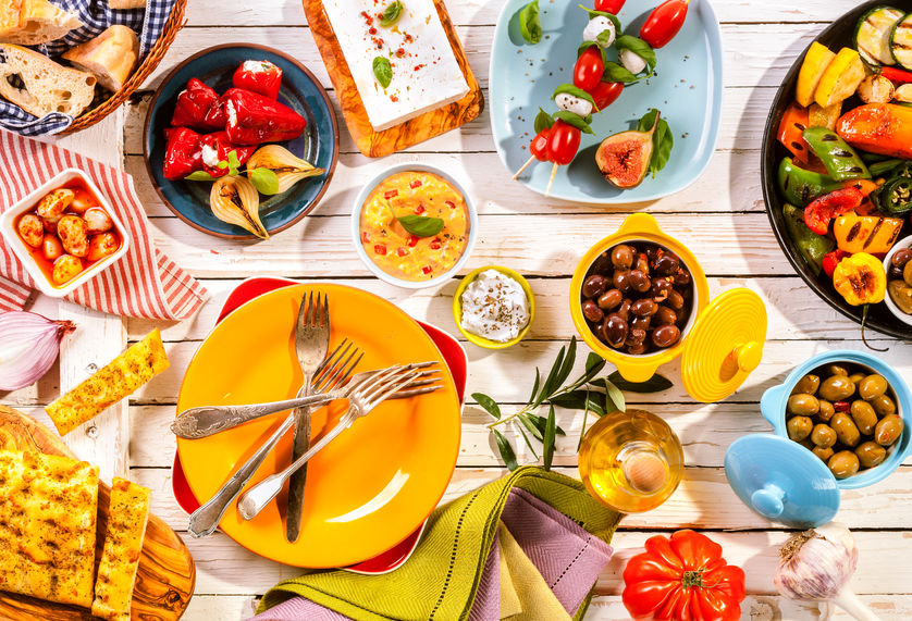 41699356 - high angle view of prepared colorful mediterranean meal spread out on painted white wooden picnic table with bright plates and cutlery
