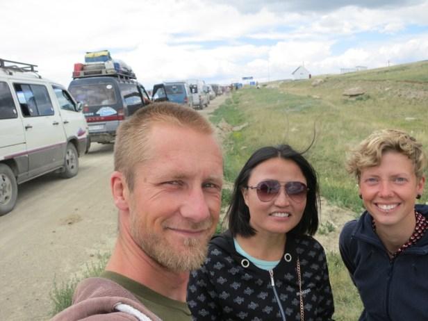 Wir mit Soni im Niemandsland und an der dritten Schlange. Die weißen Häuschen ganz hinten stehen in Russland.