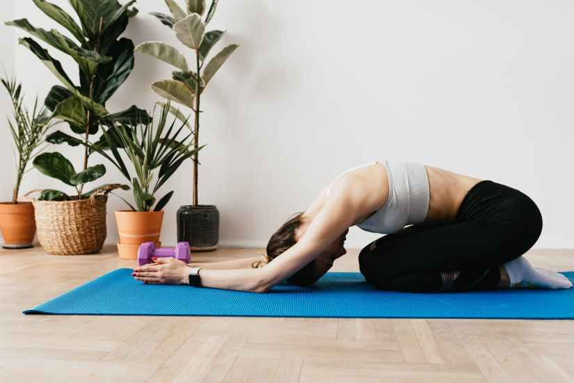 slim sportswoman stretching in child pose
