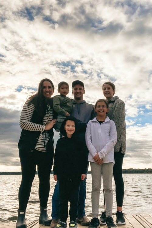 family standing in front of a lake with clouds in the sky