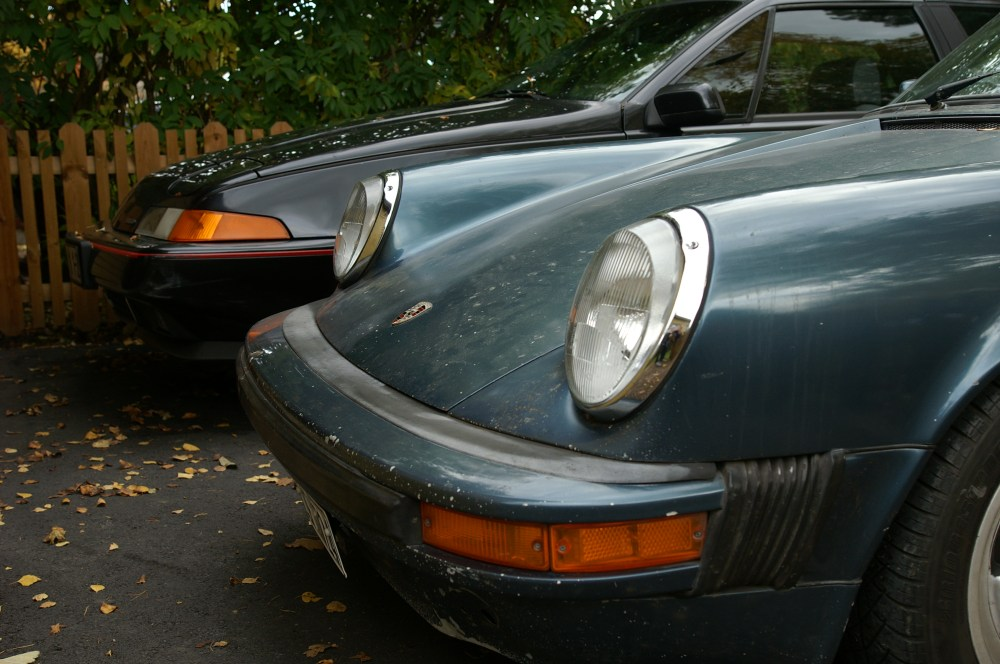 medium resolution of the front ends of a blue porsche 911 sc and a black volvo 480 turbo