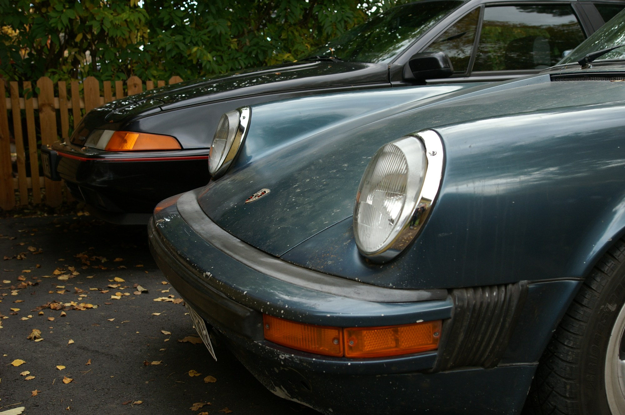 hight resolution of the front ends of a blue porsche 911 sc and a black volvo 480 turbo