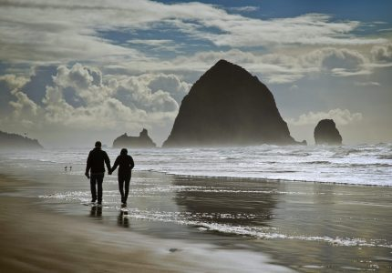 Looking at Haystack Rock, Cannon Beach, Oregon, a couple is strolling along the shoreline