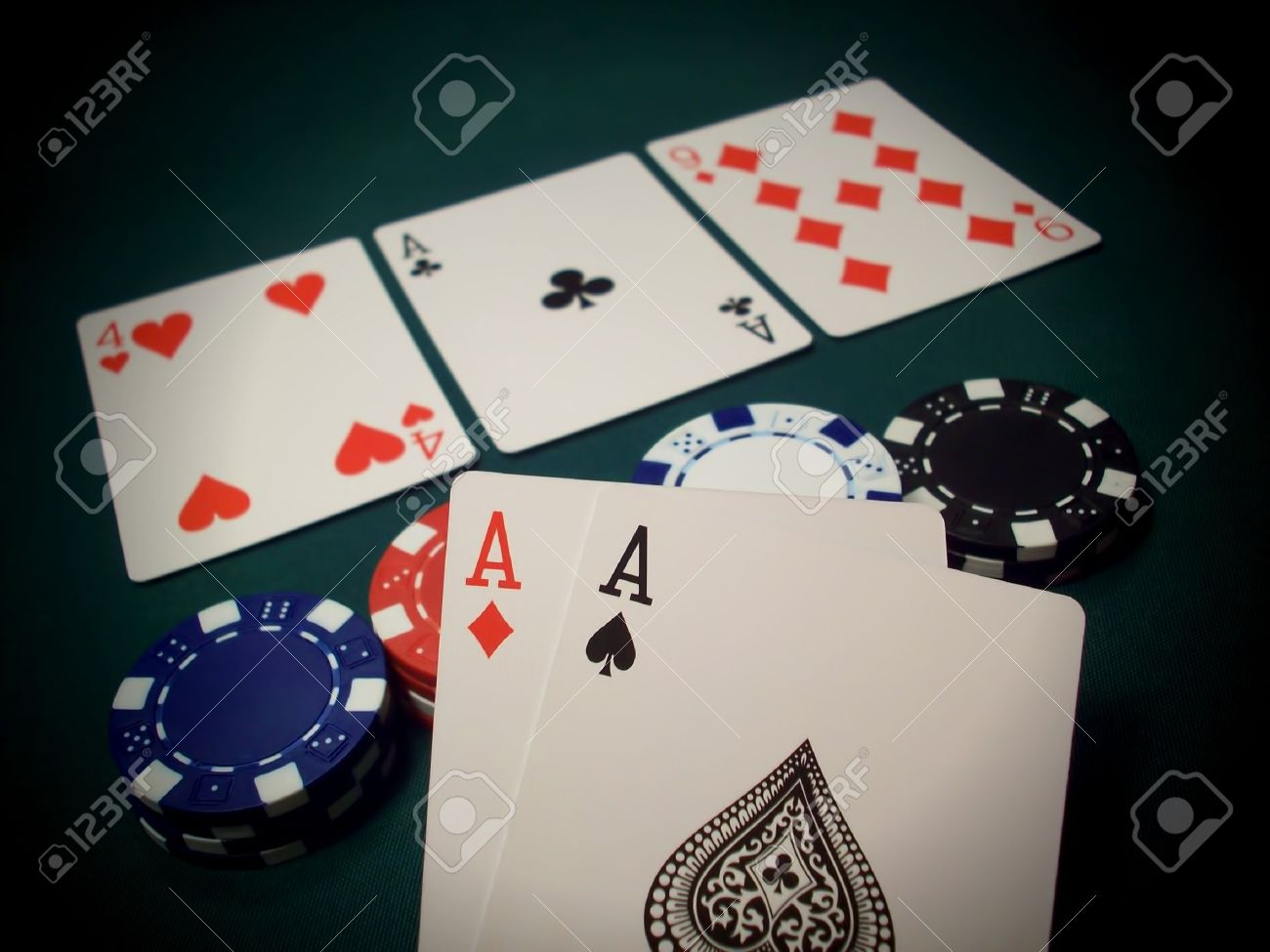 9739116-Three-cards-face-up-and-multi-colored-poker-chips-on-a-green-felt-table-This-is-known-as-The-Flop-in-Stock-Photo