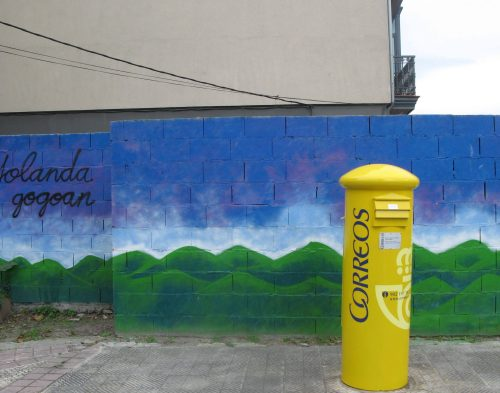 yellow postbox in front of painted mountain panorama