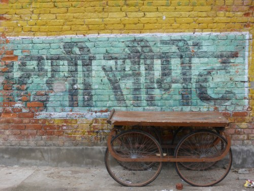 faded sign on wall and handcart