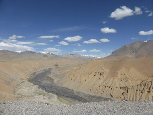 dry river valley, blue sky, fluffy clouds