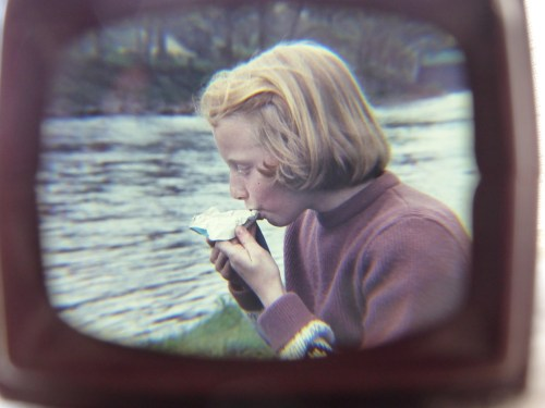 girl eating snack by stream