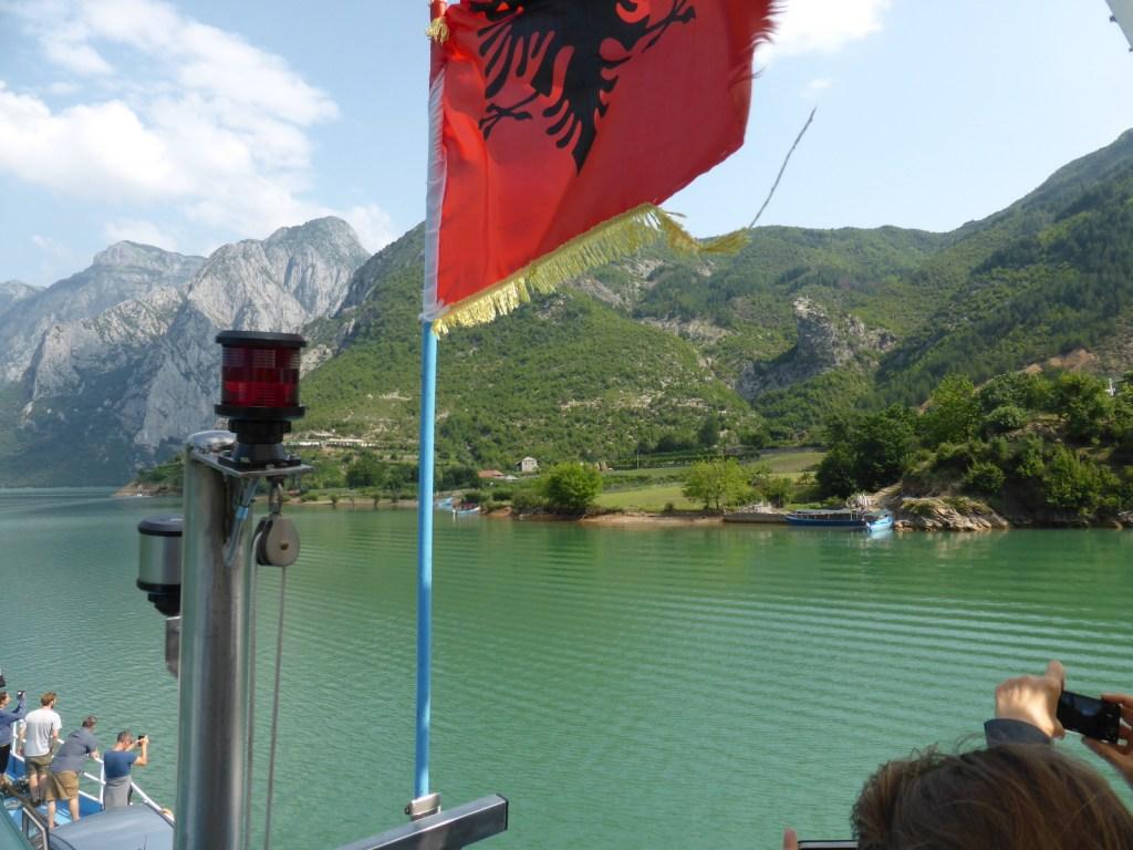 red flag against deep green lake