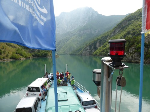 ferry travelling up lake with blue flag