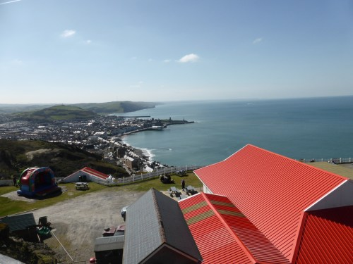 vivid red metal cafe roof points to Aberystwyth seafront below