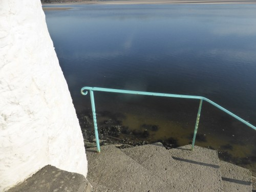 pale blue railing against deep blue still water