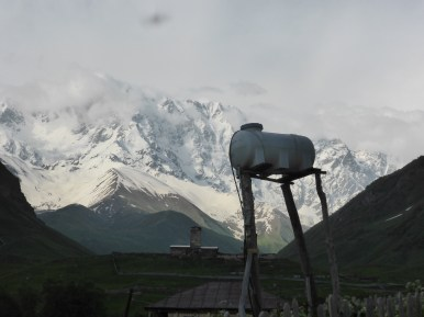 raised water tower against snowy mountains