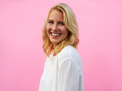 A blonde woman in a white shirt against a pink background