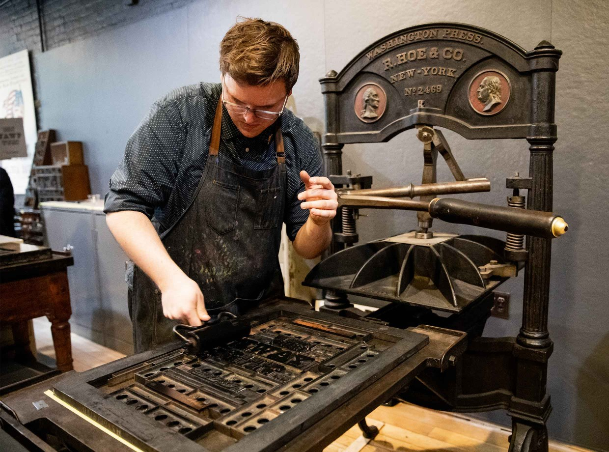 A man in an apron rolls ink onto a letterpress